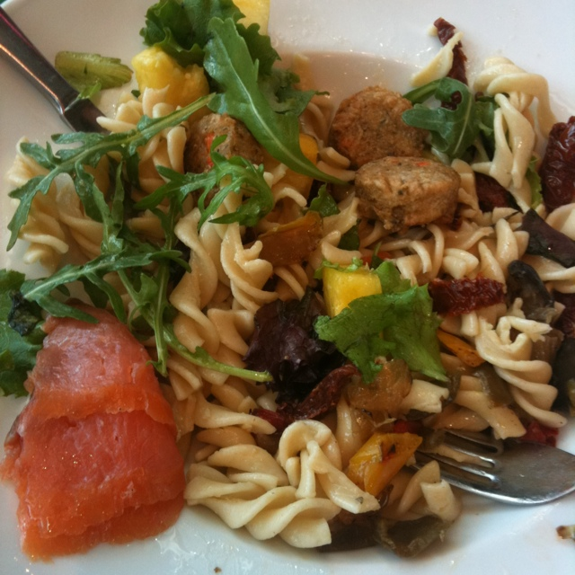 fussili pasta with sun dried tomatoes, sausage, yellow peppers, arugula, and a small piece of raw salmon